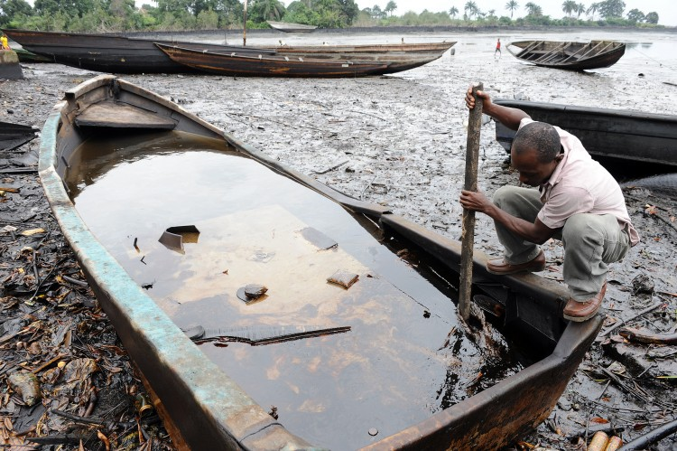 An indigene of Bodo, Ogoniland region in Rivers State, tries to separate with a stick the crude oil from water in a boat at the Bodo waterways polluted by oil spills attributed to Shell equipment failure August 11, 2011. The Bodo community in the oil-producing Niger Delta region sued Shell oil company in the United Kingdom, alleging that spills in 2008 and 2009 had destroyed the environment and ruined their livelihoods. The UN released a report this month saying decades of oil spills in the Nigerian region of Ogoniland may require the biggest cleanup ever undertaken, with communities dependent upon farmers and fishermen left ravaged. (Pius Utom Ekpei/AFP/Getty Images)