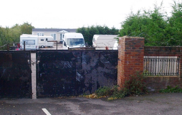 A sealed gate to the the Green Acres caravan site is pictured in Leighton Buzzard, north of London, on September 12, 2011. British police raided a travellers' site Sunday to rescue 24 men they said had been held as slaves and forced to live in squalor, some for up to 15 years. More than 200 officers from Bedfordshire Police entered the Green Acres caravan site and arrested four men and one woman, all residents on the site, on suspicion of slavery offences. (Max Nash/AFP/Getty Images)