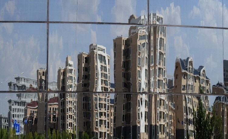 Empty apartment buildings are reflected in a window in the city of Ordos, Inner Mongolia on Sept. 12, 2011. The city which is referred to as a 'Ghost Town' due to it's lack of people, is being built to house 1.5 million inhabitants. (Mark Ralston/AFP/Getty Images)