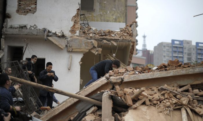 Huang Sufang (C) reacts after attempting to protect her home as workers move in for demolition orders in Yangji village, Guangzhou, south China's Guangdong province on March 21, 2012. (STR/AFP/Getty Images)