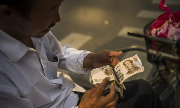 A man checks Chinese yuan bills in Beijing on July 28, 2015. (Fred Dufour/AFP/Getty Images)