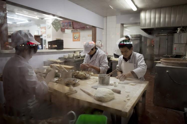 Chefs make dumplings inside a restaurant