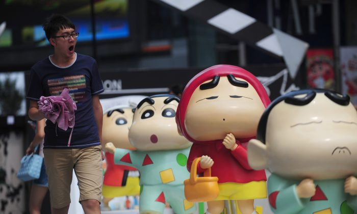 A man walking by sculptures during a Crayon Shin-chan exhibition in Shenyang, northeast China's Liaoning province on This photo taken on July 11. (STR/AFP/Getty Images)