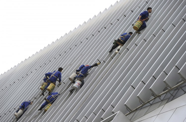 Workers clean the facade of a building i