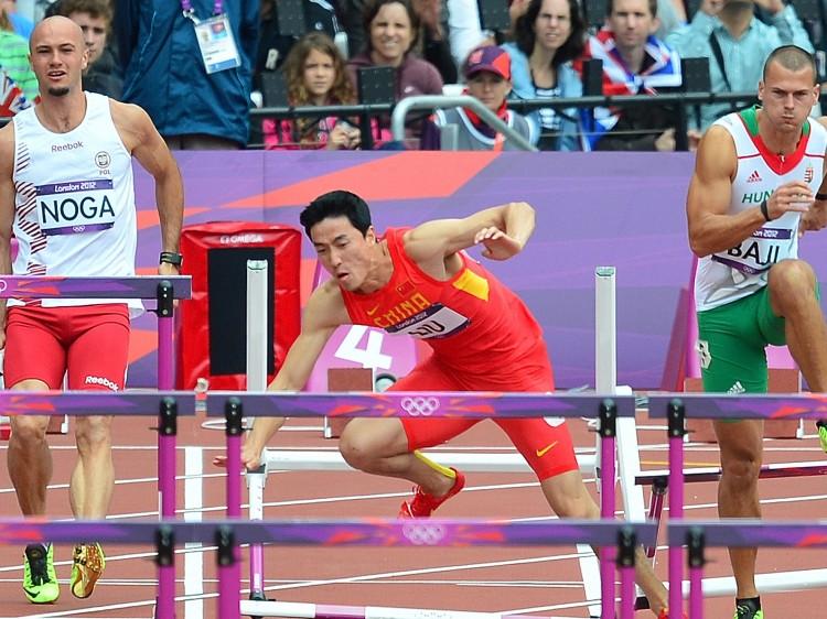 China's Liu Xiang (C) falls at the preliminaries