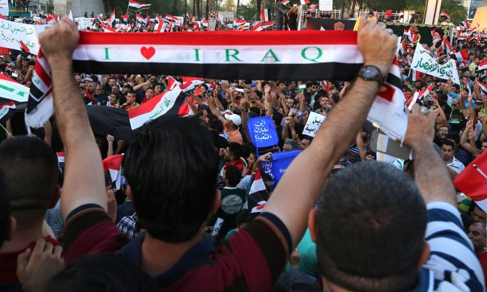 Demonstrators chant in support of Iraqi Prime Minister Haider al-Abadi as they wave national flags during a demonstration in Tahrir Square in Baghdad, Iraq, on Aug. 14, 2015. (Karim Kadim/AP)