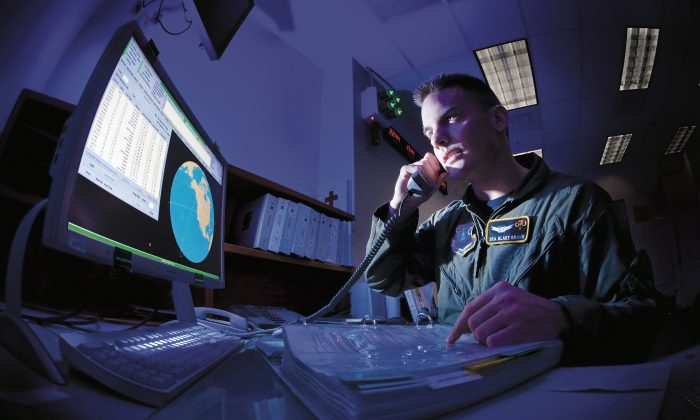 Senior Airman Blake Braun responds to a phone call from the Joint Space Operations Center at Vandenberg Air Force Base, Calif. Braun, a space systems operator with the 7th Space Warning Squadron, works to identify, track, and categorize space objects. (U.S. AIr Force photo/Lance Cheung)