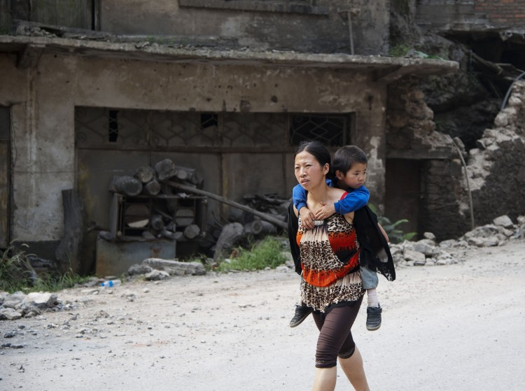 This photo taken on September 8, 2012 shows a woman carrying her child on her back along a street in Yiliang after two quakes hit the area on the border of southwestern Yunnan and Guizhou provinces an hour apart around the middle of the day followed by a string of aftershocks. (STR/AFP/GettyImages)