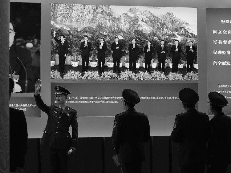 policeman poses for photo in front of the photo of Hu Jintao while visiting an exhibition