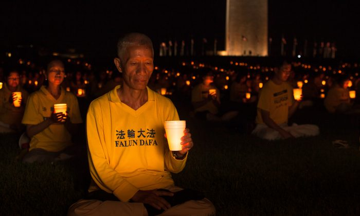 Practitioners of Falun Dafa (also Falun Gong) hold a candle light vigil by the Washington Monument on July 16, 2015, to commemorate the 16 years their fellow practitioners have been facing persecution in China. (Petr Svab/Epoch Times)