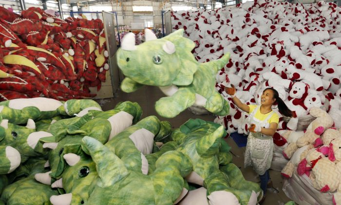 A Chinese worker stacking soft toys at a factory before packing them for export, in Lianyungang, China's Jiangsu province on Sept 6, 2015. (STR/AFP/Getty Images)