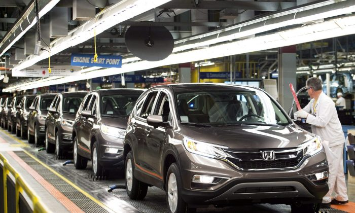 Workers inspect cars on the assembly line at a Honda plant in Alliston, Ontario on March 30, 2015. The transportation sector continues to lead the rise in Canadian manufacturing. (The Canadian Press/Nathan Denette)