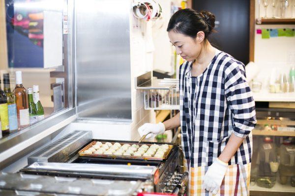 Aya Tatsushiro makes takoyaki, or octopus balls, at Mocu-Mocu. (Samira Bouaou/Epoch Times)