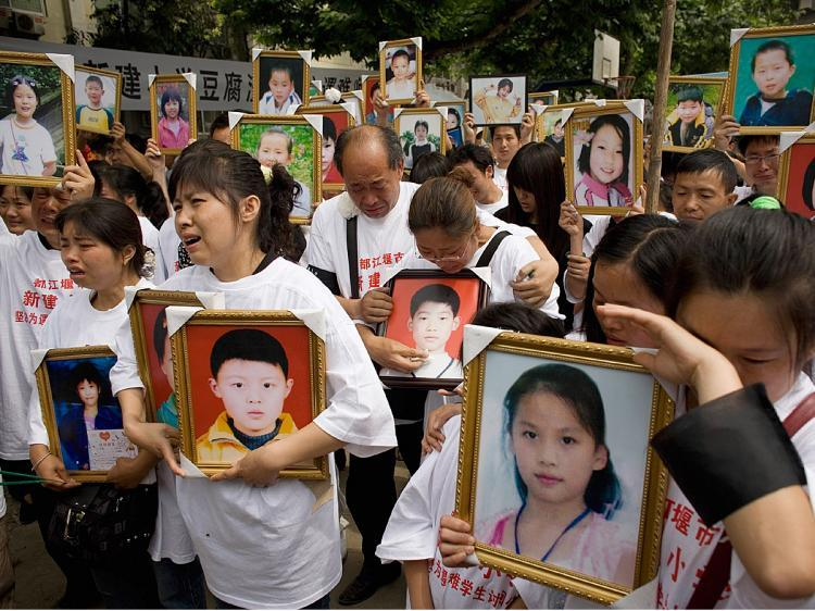Parents of pupils killed when the Xinjian primary school collapsed in the May 12 earthquake cry as they hold portraits of their loved ones during a commemoration of Children's Day on the rubble-strewn school campus on June 1, 2008 in Dujiangyan, China. (Andrew Wong/Getty Images)