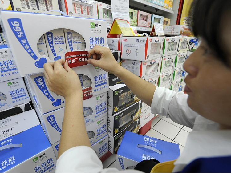 A saleswoman places a label saying 'Does not contain melamine' onto packs of liquid milk for sale at a supermarket in Chengdu, China, September 26, 2008, after at least 53,000 infants were poisoned by the industrial additive. (Liu Jin/AFP/Getty Images)