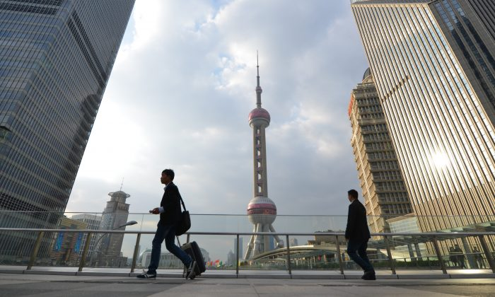 Pedestrians walk through the financial district of Shanghai on Oct. 16, 2013. Two major Chinese financial firms are set to raise billions in upcoming initial public offerings. (Peter Parks/AFP/Getty Images)