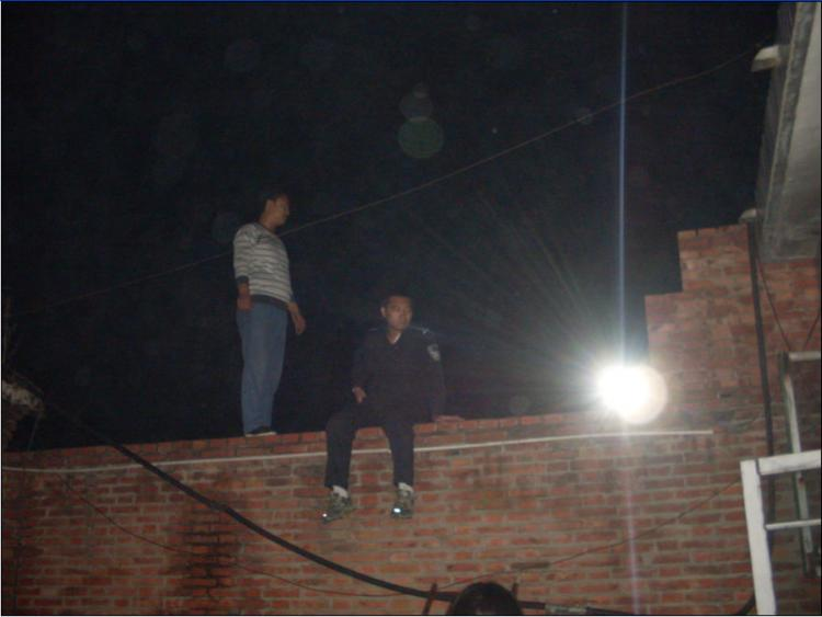 A uniformed man identified as Zhang Songwei, deputy head of the Yinliu Police Station, sits on a wall at night outside the girls' home. (Minghui.net)