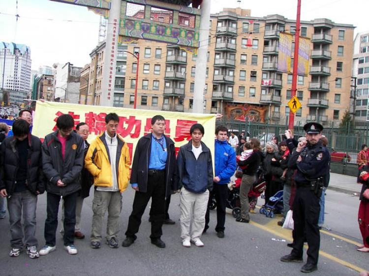 Several men form a human barrier to prevent the Falun Gong from marching a block behind the 2009 Chinatown parade. The group's application to join the parade has been denied every year since 2003 while other groups have been accepted. (The Epoch Times)