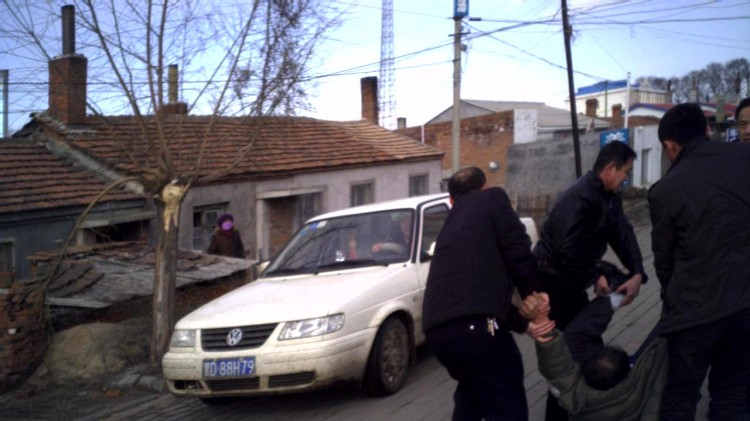 SILENCING THE FAMILY: Prison guards drag Mr. Li Shaotie, 60, to a police car after he refused to show his ID when trying to visit a relative imprisoned at Jiamusi.(Minghui.org)