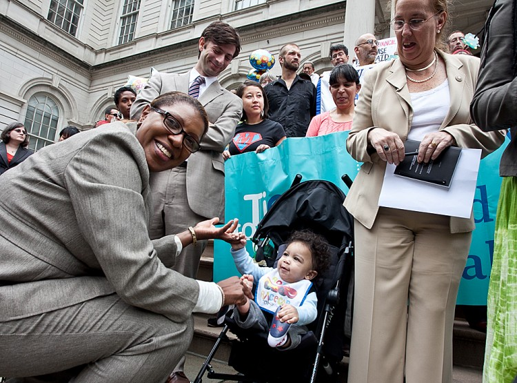Councilwoman Letitia James plays with a child at a protest calling for New York City Council to pass a law mandating paid sick days Oct. 4. (Amal Chen/The Epoch Times)