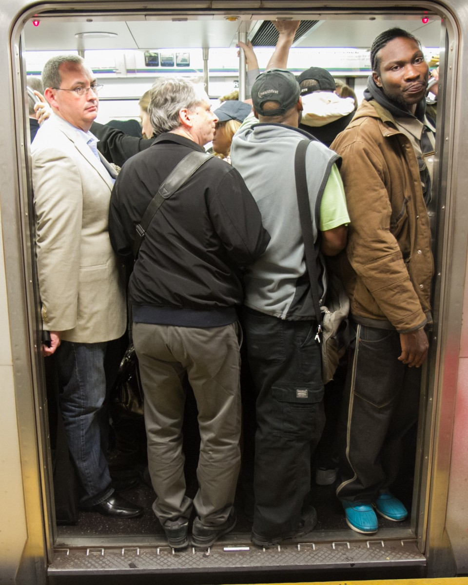Commuters board a crowded No. 6 train heading to Grand Central Terminal during rush hour on Oct. 8 in New York. (Benjamin Chasteen/The Epoch Times)