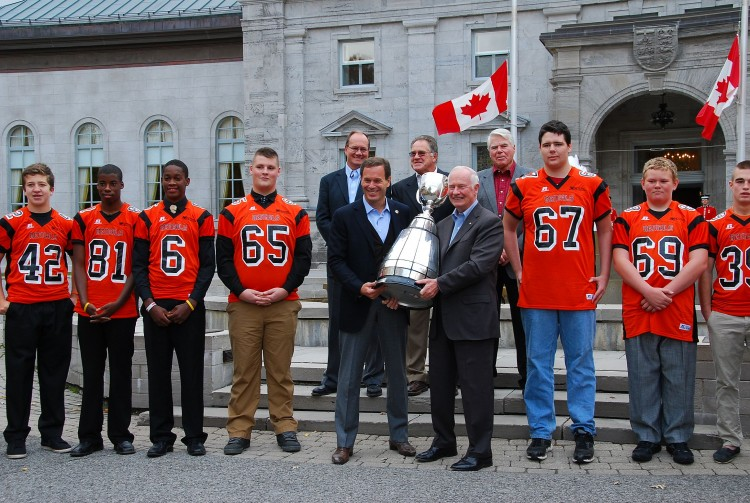 Canadian Football League (CFL) Commissioner Mark Cohon (L) and Governor General of Canada David Johnston hold the Grey Cup outside Rideau Hall, the Governor General's official residence, alongside members of the Orleans Bengals Football Club and former CFL greats, on Oct. 21, 2012. (Jonathan Ren/The Epoch Times)
