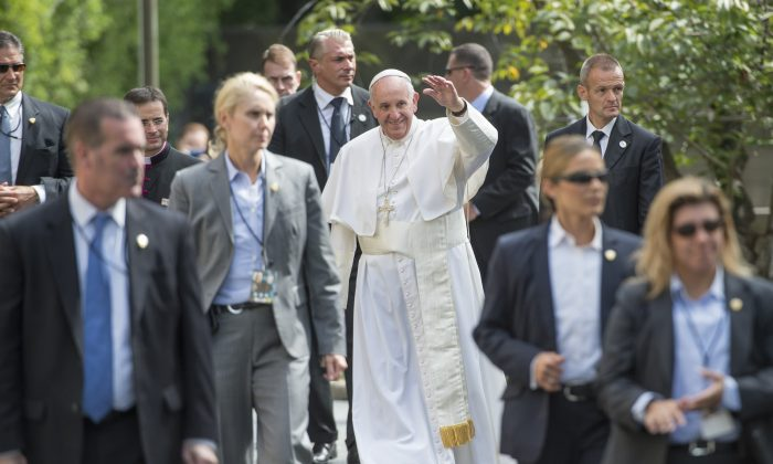 Pope Francis, surrounded by security, waves to well-wishers at the Apostolic Nunciature to the United States upon returning from his trip to Capitol Hill, on September 24, 2015 in Washington, DC.       (MOLLY RILEY/AFP/Getty Images)