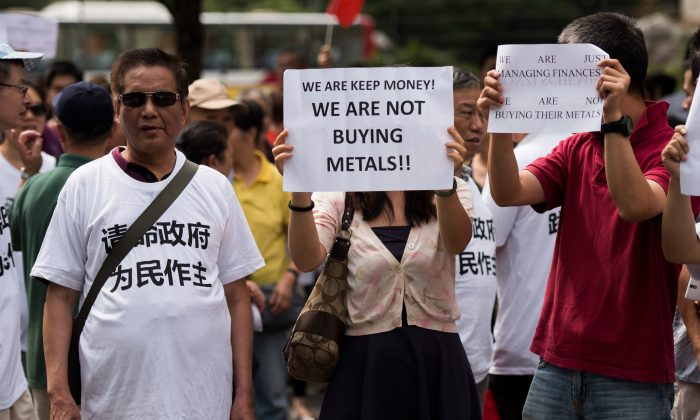 Protesters against the Fanya metals exchange hold placards outside the office of the China Insurance Regulatory Commission in Shanghai on Sept. 25. (Johannes Eisele/AFP/Getty Images)