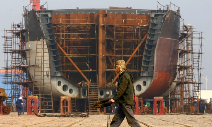 A worker walks the giant hulk of a ship being built at a state-owned company dock in Chongqing on Feb. 12, 2009. (China Photos/Getty Images)