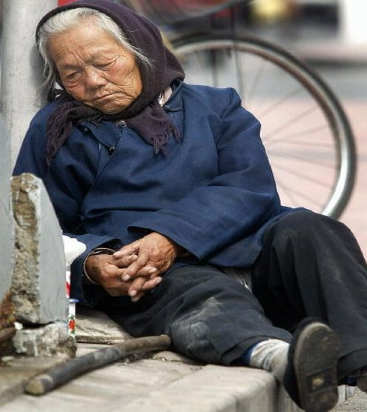 An elderly woman rests beside a pedestrian overpass in Beijing. (Frederic J.Brown/AFP/Getty Images)
