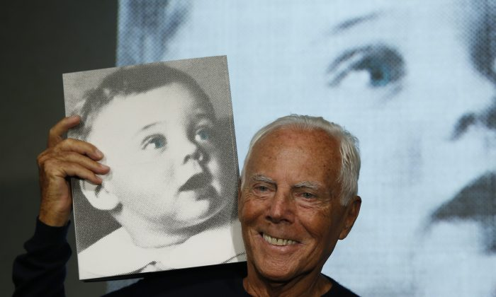Italian fashion designer Giorgio Armani poses for photographers holding a copy of the book 'Giorgio Armani' written by journalist Suzy Menkes, presented at the end of unveiling of his women's Spring-Summer 2016 collection, part of the Milan Fashion Week, in Milan, Italy, on Sept. 28, 2015. (AP Photo/Luca Bruno)