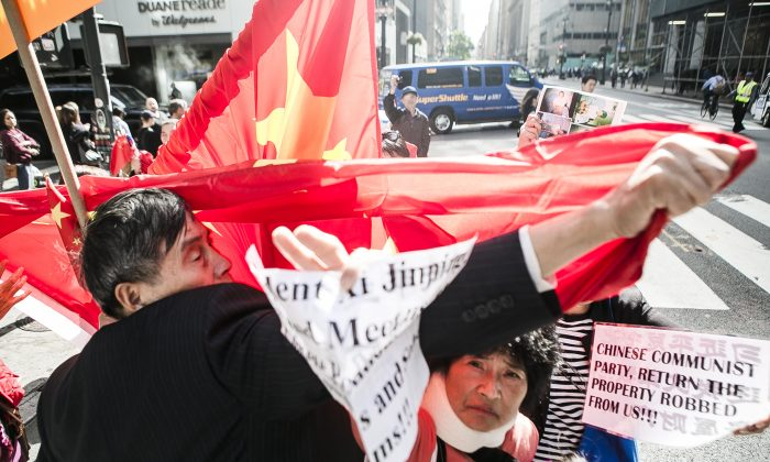 Chinese people who oppose the Chinese Communist Party (CCP), many of them who've had their land confiscated by authorities, are harassed by supporters of the CCP by blocking their messages with Chinese flags near the Waldorf Astoria on Lexington Ave. between 48th Street and 47th Street in New York where Chinese Communist Party leader Xi Jinping is staying, on Sept. 26, 2015. Supporters of the CCP try to cover Fu Yuxia with the Chinese flag in an attempt to block her message (President Xi Jinping, Stop and Meet us, the Chinese Petitioners. Listen to us and Solve our Problems!!!). (Samira Bouaou/Epoch Times)
