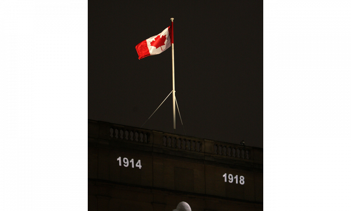 """A Canadian flag flies above an image of a solider projected onto Canada House in Trafalgar Square in London, England, during the """"Vigil 1914-1918"""" ceremony. The vigil, a week-long tribute to Canadians lost during World War I, is also taking place in Ottawa, Fredericton, Halifax, Toronto, Regina, and Edmonton. (Oli Scarff/Getty Images)"""