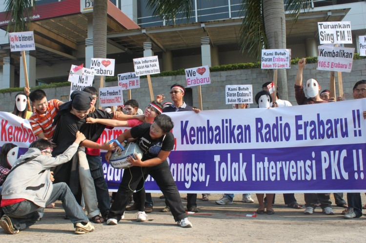 Fans of the Indonesian Radio Erabaru perform outside the headquarters of Sing FM a re-enactment of the forced shutdown of the station by government authorities on Sept. 13, as fellow protesters hold placards and banners that call for the restoration of Ra (Courtesy of Radio Erabaru)
