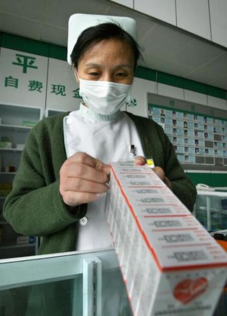 A hospital worker at a dispensary stocks up on medicine for general health in Beijing. Chinese counterfeit medicines have likely caused hundreds if not thousands of deaths outside of China in recent years. (Frederic J. Brown/AFP/Getty Images)