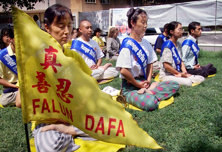 Falun Gong practitioners meditate as they enter the fourth day of a hunger strike