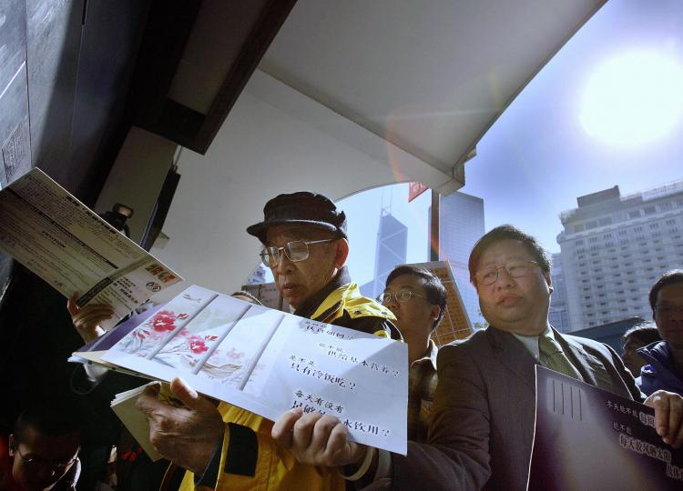 Hong Kong pro-democracy activists carry collected 3,000 Christmas cards and 2,000 post cards to mail out in Hong Kong, December 22, 2005. The Christmas and post cards were sent to Beijing for victims of June 4 Tiananmen Square massacre. (Samantha Sin/Getty Iamges )