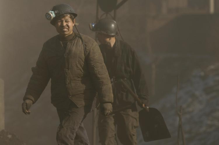 Coal miners walk through thick coal dust. The Chinese coal industry is the most dangerous in the world for deaths through both accidents and disease. (Peter Parks/AFP/Getty Images)