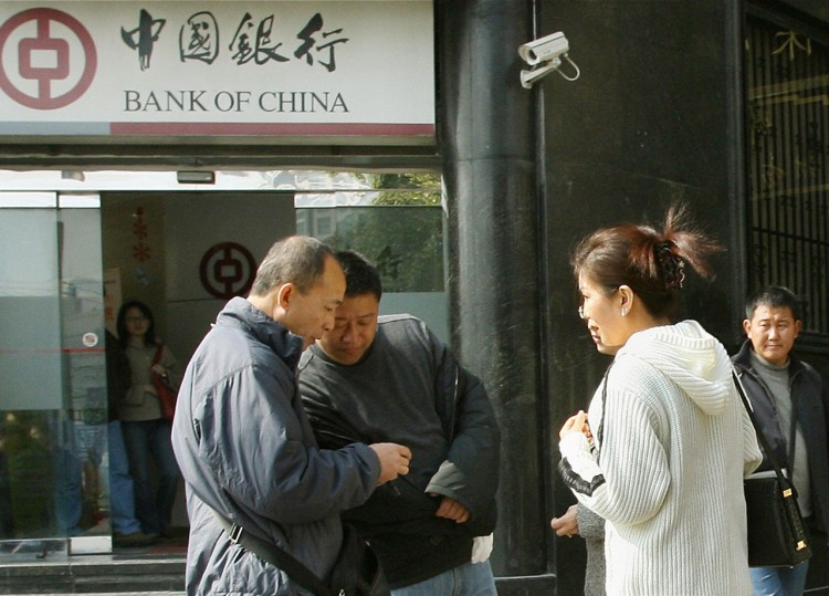 A distorted economy has given rise to a private lending crisis in several cities in China. Chinese blackmarket moneychangers trade foreign currency for renminbi (yuan) with two customers (R) outside a branch of the Bank of China in Shanghai, Feb. 7, 2007. (AFP/Getty Images)