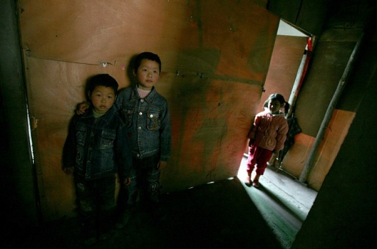 China's Vulnerable 'Left-behind Children:' Chen Xi (L), Chen Zhou (C), and Liang Xiaoyan, who all live with their grandmothers, plays at a house on March 5, 2007 in Chongqing, China. (China Photos/Getty Images)