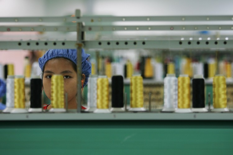 A worker labors before the spinning machine at the production line of Dongguan Da Lang Wealthwise Plastic Factory on Sept. 4, 2007 in Dongguan, Guangdong Province. The recent closing of Dingjia Knitting Company has caused growing fears of widespread bankruptcy in the area. (Feng Li/Getty Images)