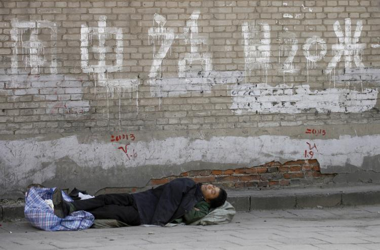 A petitioner sleeping on a deserted street of what's left of a 'petitioners' village,' which has been demolished ahead of the Olympics.  (Peter Parks/AFP/Getty Images)
