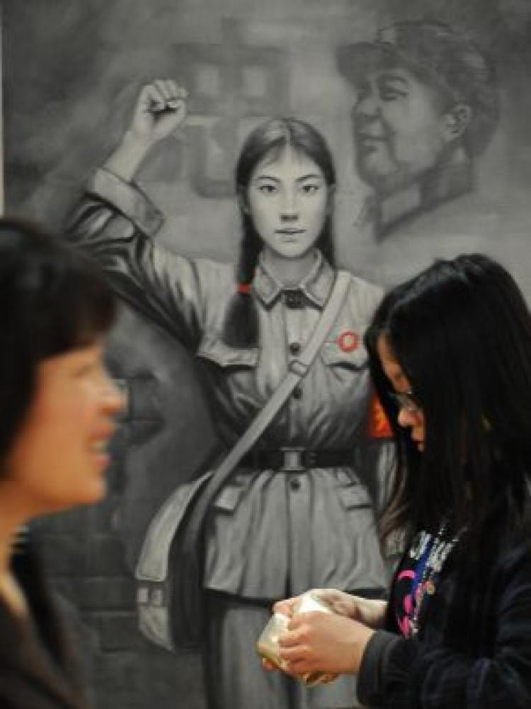 Two Chinese women walk past a painting of a Red Guard from China's Cultural Revolution period at an art exhibit in Shanghai. Parts of a 1950s devotional hymn to the Chinese Communist Party were changed or cut for the Olympics opening ceremony and internet censors have worked hard to keep stories of the singer switch off Chinese websites. (Mark Ralston/AFP/Getty Images)