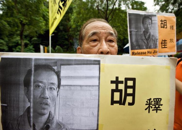 An elderly man holds a placard with the image of jailed Chinese rights campaigner Hu Jia.  (Andrew Ross/AFP/Getty Images)