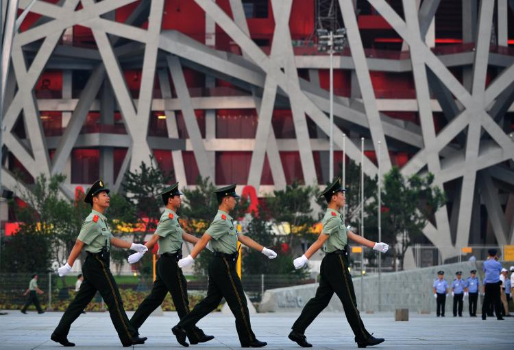 Chinese paramilitary soldiers march outside the main Olympic Stadium, also known as the Bird's Nest, in Beijing. (FREDERIC J. BROWN/AFP/Getty Images)