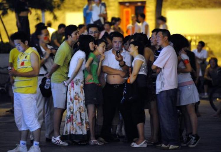 Chinese residents gather around to watch the Beijing Olympics in Beijing.  (Goh Chai Hin/AFP/Getty Images)