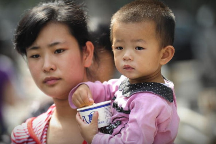A mother leaves a children's hospital with her child in Beijing on September 22, 2008 as China's toxic milk scandal escalated after officials admitted nearly 53,000 children had been sickened by contaminated products and more countries moved to ban or lim (Peter Parks/AFP/Getty Images)