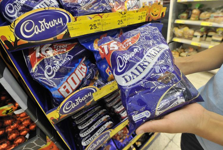 A shopper holds up a selection of Cadbury chocolates at a supermarket in Hong Kong . (Mike Clarke/AFP/Getty Images)