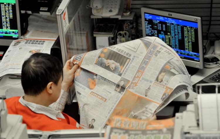 A trader reads newspaper at the Hong Kong Stock Exchange. ( Mike Clarke/AFP/Getty Images)