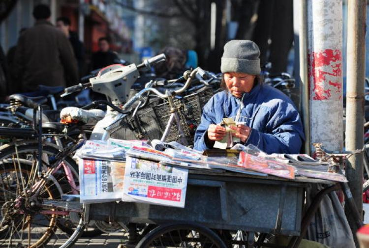 A newspaper vendor counts her one yuan (or RMB) notes in Beijing.  (Frederic J Brown/AFP/Getty Images)